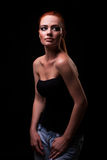 Red head model in jeans on black background Stock Photos