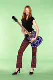 Red Head Rock and Roll Guitar Player with Tounge Stud. Female Red Head Rock and Roll Guitar Player with Tounge Stud Stock Photo