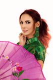 Red head woman in asian dress behind umbrella Stock Photo