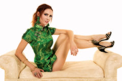 Red head woman in Asian dress sit on sofa Stock Photo