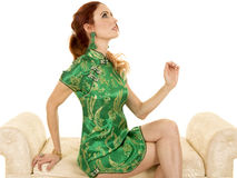 Red head woman asian dress sit on sofa look up Royalty Free Stock Photography