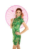 Red head woman Asian dress with umbrella behind her Royalty Free Stock Photos