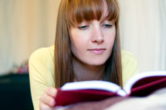 Red head woman reading book at home stock image