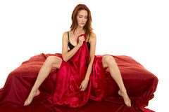 Red head woman sitting wrapped in red sheet legs out Stock Photography