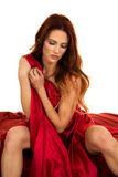Red head woman sitting wrapped in red sheet look down Royalty Free Stock Photo