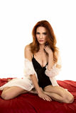Red head woman in white night gown over black kneel looking Stock Photography