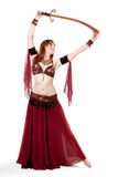 Red-headed belly dancer posing with sword Royalty Free Stock Photography