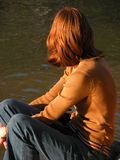 Red-headed girl by river. Red-headed girl sitting by the Murray River, Australia Royalty Free Stock Photography
