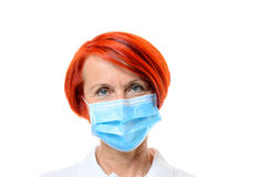 Red headed nurse wearing blue face mask on white Royalty Free Stock Image