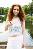 Red-headed nymph of the lake. Portrait of a beautiful red-headed girl posing near the lake royalty free stock images