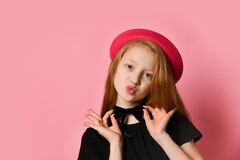 Free Red-headed Teenager In Black Dress And Red Hat. She Kissing You, Holding On To Choker, Posing On Pink Studio Background. Close Up Royalty Free Stock Photography - 170016437