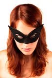 Red-headed woman in the mask. Beautiful red-headed girl in black mask looking straight to the camera stock images