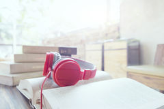 Red headphone on book in cafe or library. Soft focus and soft sunlight in the morning feel relax Stock Photos