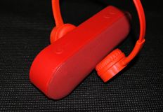 Red headphones and music speaker on a black background royalty free stock photos