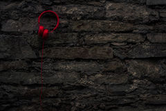 Red headphones on wall. Red headphones hanging on old stone wall Royalty Free Stock Photography