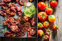 Red and healthy tomatoes dried in the sun. On wooden table stock photo