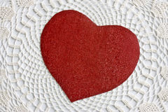 heart on lace. A red cutout heart on a white lace background Stock Image