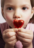 Red heart. Child presenting red candy heart stock images