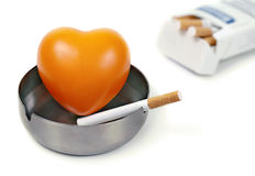 Red heart in the ashtray and cigarettes. Royalty Free Stock Image