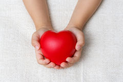 Red heart in baby palm hands Royalty Free Stock Photos