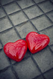 Red heart background. Two red heart shapes on a gray tiled floor like a Valentine background Royalty Free Stock Photography