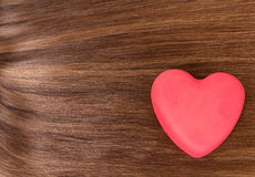 Red heart on a background of long, hair brown. Red heart on a background of long, well-groomed hair brown Royalty Free Stock Photos