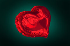 Red heart balloon against green background Stock Image