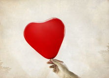 Red heart balloons in hand, vintage background Royalty Free Stock Photo