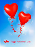 Red heart balloons with ribbons in blue sky. Royalty Free Stock Photo