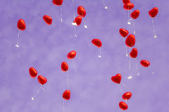 Red heart balloons in the sky - symbol of love. A group of beautiful heart ballons in front of a purple sky. Perfect for illustrating e.g. weddings, Valentine's Royalty Free Stock Image