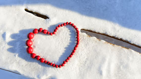 Red heart of beads on wood and snow background. Stock Images