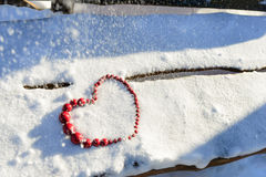 Red heart of beads on wood and snow background. Valentine`s Day Royalty Free Stock Photo