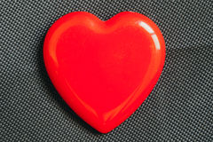 Red heart on black fabric texture fo valentine background. Stock Images