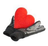 Red heart in black leather gloves. Composition of the red heart in black leather gloves, isolated over the white background Royalty Free Stock Photos