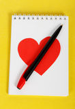 Red heart with a black pen on white notebook Royalty Free Stock Images