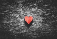 Red heart on black wooden background stock photography