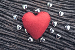 Red heart on black wooden background with small siver hea. Heart, red heart on black wooden background with small siver heart Royalty Free Stock Photos