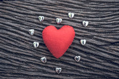Red heart on black wooden background with small siver hea. Heart, red heart on black wooden background with small siver heart Stock Photo