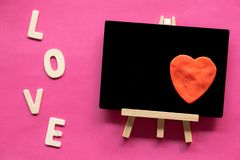 Red heart in Blackboard and word LOVE on pink background, Love icon, valentine`s day. Relationships concept with copy space royalty free stock photography