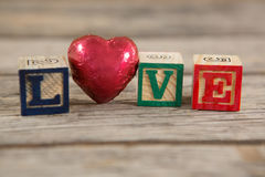 Red heart between blocks displaying love message Stock Photos