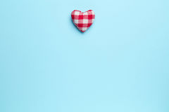Red heart on blue background. Plain blue background with single red heart Royalty Free Stock Image