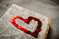 Red heart on the book on the textured background. Red heart on the old book on the textured background Royalty Free Stock Photo