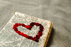 Red heart on the book on the textured background. Red heart on the old book on the textured background Royalty Free Stock Image