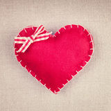 Red heart with a bow on vintage fabric Royalty Free Stock Images
