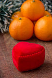 Red heart box for jewelry gift. Orange mandarines and red heart box Royalty Free Stock Photos