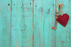 Red heart and bronze skeleton key hanging on antique green wood door. Red heart with stars and metal skeleton key hanging by rope on antique turquoise wooden Stock Photo