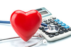 Red heart and calculator with stethoscope on white background Royalty Free Stock Photography