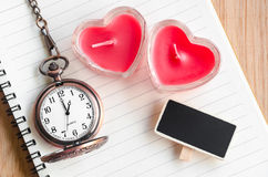 Red heart candle and pocket watch. Royalty Free Stock Photo