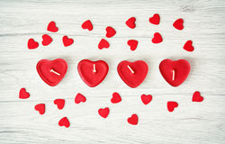 Red heart candles with little decorative hearts on the wooden ba Royalty Free Stock Photography