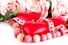Red heart candles, necklace and roses. Red heart candles, wooden necklace, ribbon and roses on white background Stock Image